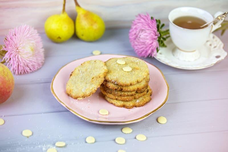Cozeu recentemente cookies do coco com chocolate branco em uma placa bonita, em um fundo de madeira cinzento, cercado por um copo fotos de stock