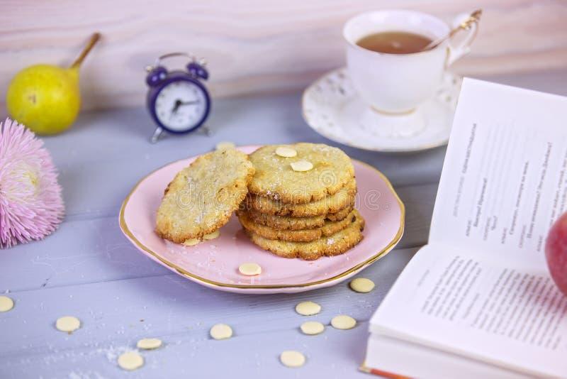 Cozeu recentemente cookies do coco com chocolate branco em uma placa bonita, em um fundo de madeira cinzento, cercado por um copo fotos de stock royalty free
