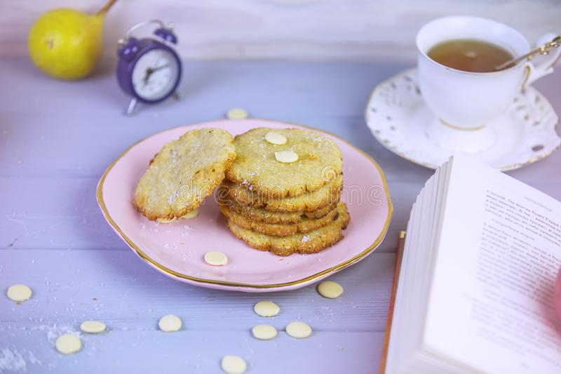 Cozeu recentemente cookies do coco com chocolate branco em uma placa bonita, em um fundo de madeira cinzento, cercado por um copo imagens de stock