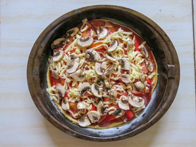 Cozeu recentemente a pizza caseiro com pepperoni, mussarela, tomates, cogumelo, presunto e manjericão Vista superior na tabela de foto de stock royalty free