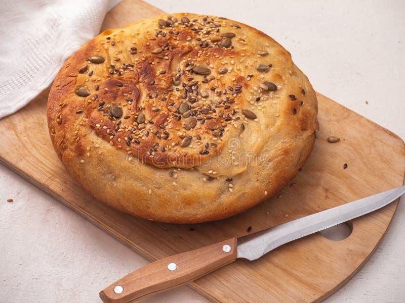 Cozido recentemente redondo-deu forma ao pão caseiro com sementes e sésamo em uma placa de madeira da cozinha imagens de stock royalty free