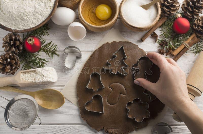 Cozimento criativo do Natal de biscoitos caseiros com mãos em um fundo branco de madeira, lugar para o texto Configuração lisa imagem de stock