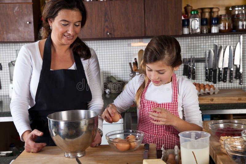 Cozimento da matriz e da filha junto na cozinha fotos de stock