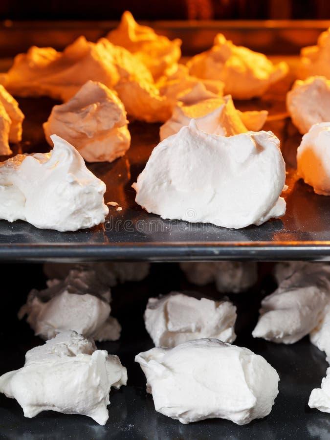 Cozimento da merengue doce da sobremesa em bandejas do forno fotografia de stock royalty free