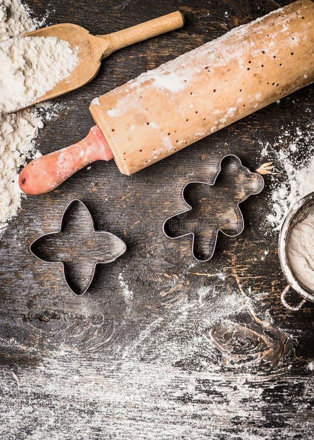 Cozimento das cookies do Natal A preparação com coze moldes, pino do rolo e farinha no fundo de madeira fotos de stock royalty free