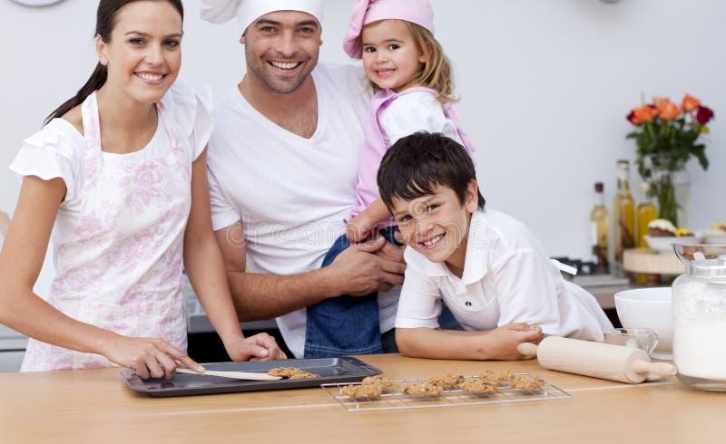 Cozimento de sorriso da família na cozinha fotografia de stock