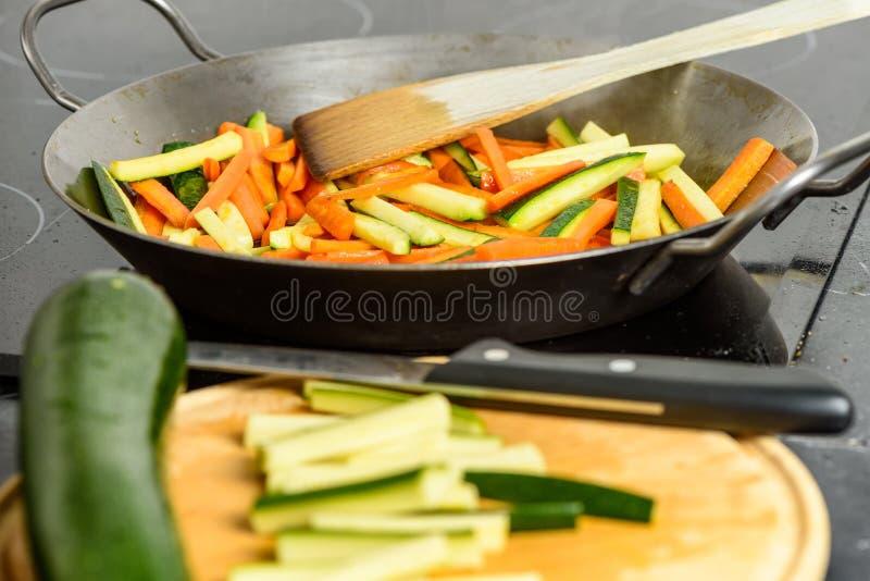 Cozimento de vegetais salteado com abobrinha e cenouras Foco na bandeja no fundo fotografia de stock royalty free