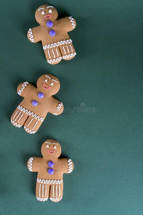 Cozimento do Natal e do feriado Cookies dos homens do gengibre com a decoração no verde Fundo verde da receita foto de stock royalty free