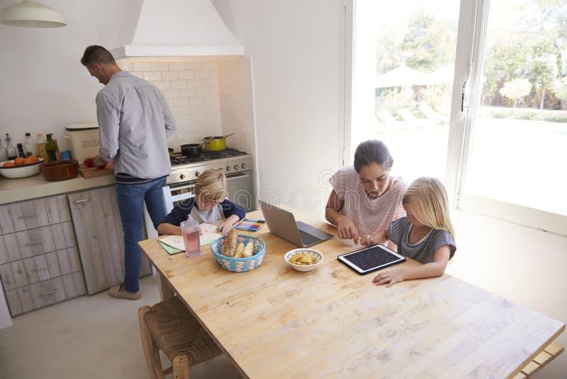 Cozimento e mum do paizinho com as crianças na mesa de cozinha, ângulo alto foto de stock royalty free