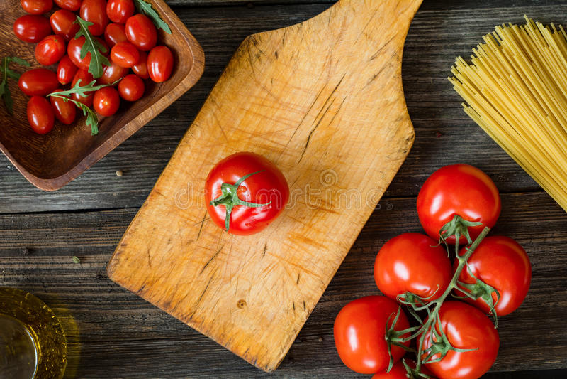 Cozimento italiano Tomates frescos, massa, azeite, especiarias na tabela de madeira foto de stock