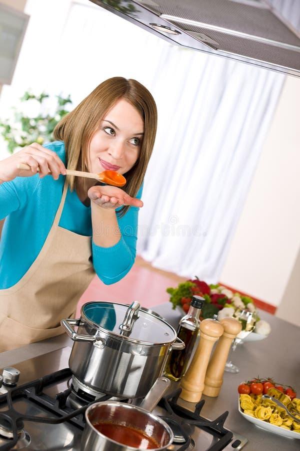Cozimento - mulher que prova o molho de tomate italiano foto de stock royalty free
