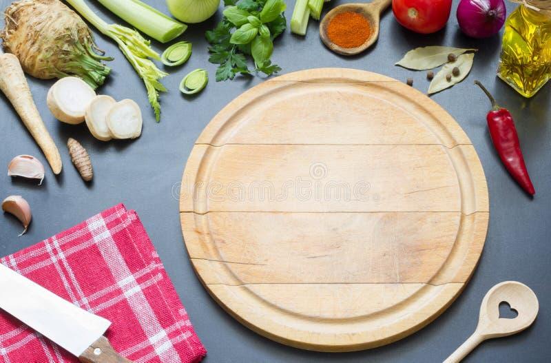 Cozimento no conceito do fundo do alimento da cozinha com vegetais das especiarias e placa de corte foto de stock royalty free