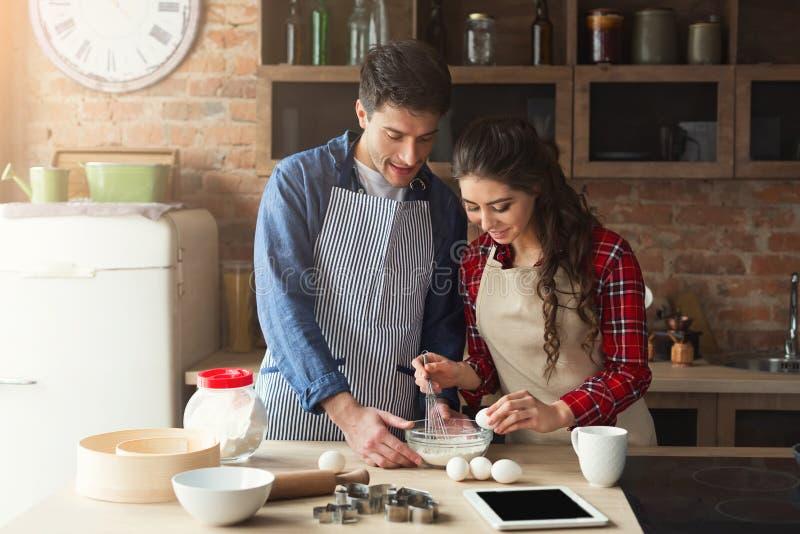 Cozimento novo feliz dos pares na cozinha do sótão foto de stock