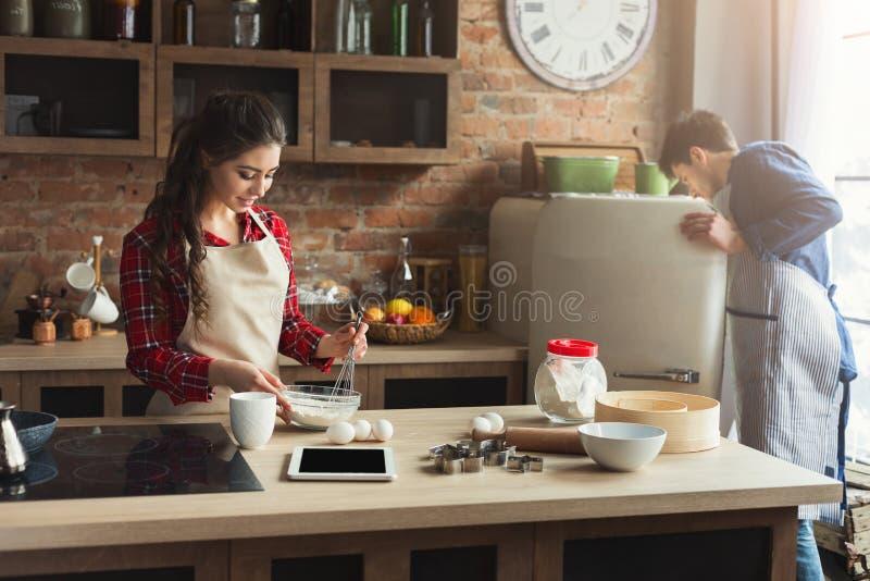 Cozimento novo feliz dos pares na cozinha do sótão fotos de stock royalty free