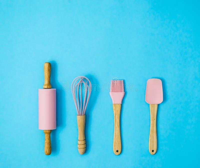 Cozimento ou ferramentas cor-de-rosa da pastelaria no fundo azul fotografia de stock