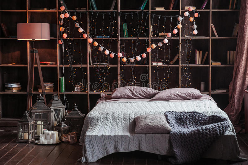 Coziness, άνεση, εσωτερικό και έννοια διακοπών - η άνετη κρεβατοκάμαρα με το κρεβάτι και τη γιρλάντα ανάβει στο σπίτι Ένα ράφι με στοκ εικόνες με δικαίωμα ελεύθερης χρήσης