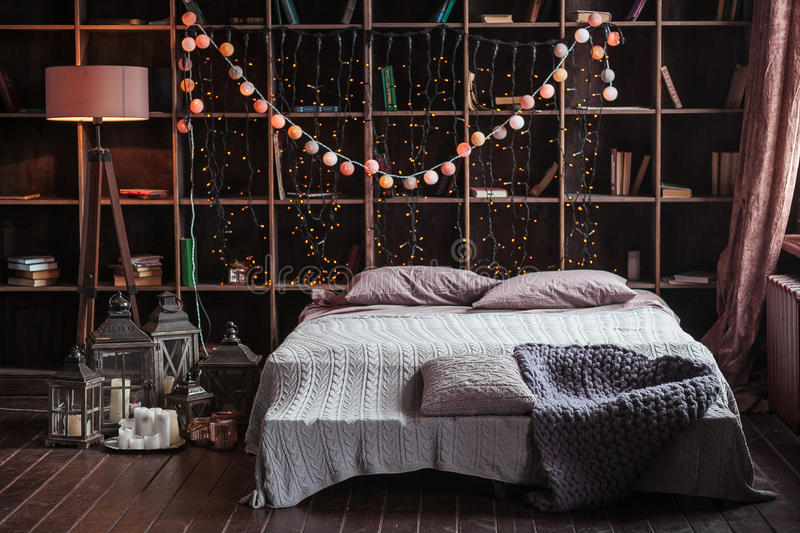 Coziness, comfort, interior and holidays concept - cozy bedroom with bed and garland lights at home. A rack with books stock photography