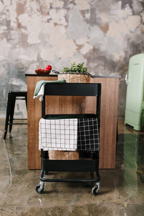 Cozinha acolhedor do sótão com tabela, as cadeiras e as cremalheiras dinning do armazenamento do metal nas rodas - trole foto de stock royalty free