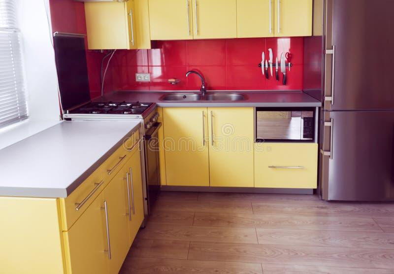 Cozinha amarela com armários, janela, estratificada imagem de stock royalty free