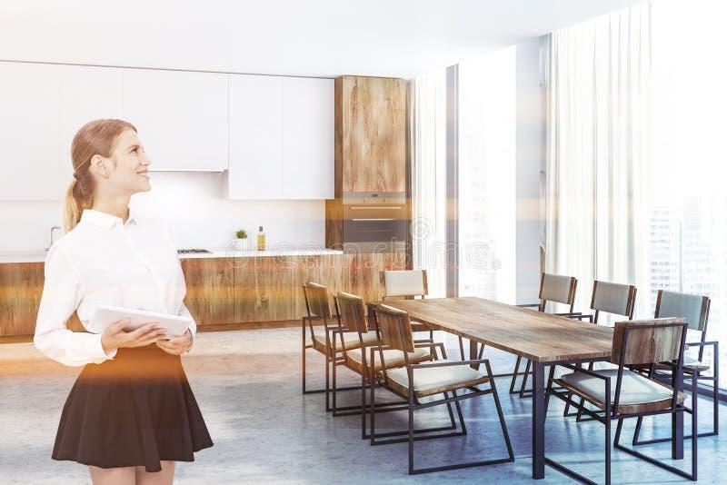Cozinha branca e de madeira, tabela longa, mulher imagem de stock