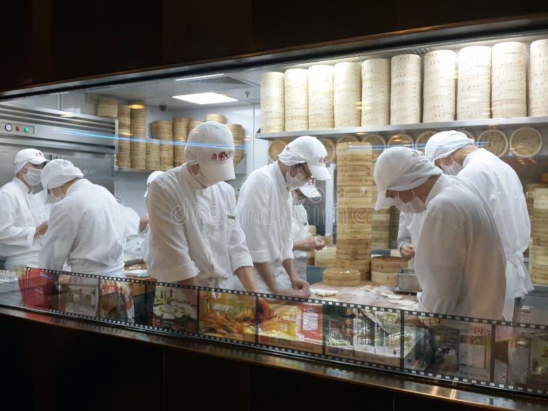 Cozinha chinesa do restaurante vista através da janela da rua Cozinheiros dos homens que cozinham refeições foto de stock royalty free