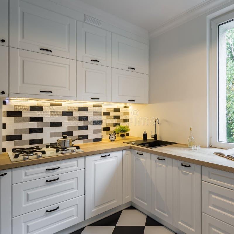 Cozinha com armários e a parede de tijolo clássicos imagem de stock