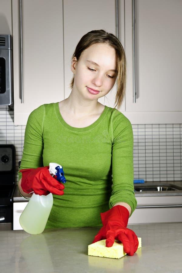 Cozinha da limpeza da menina foto de stock