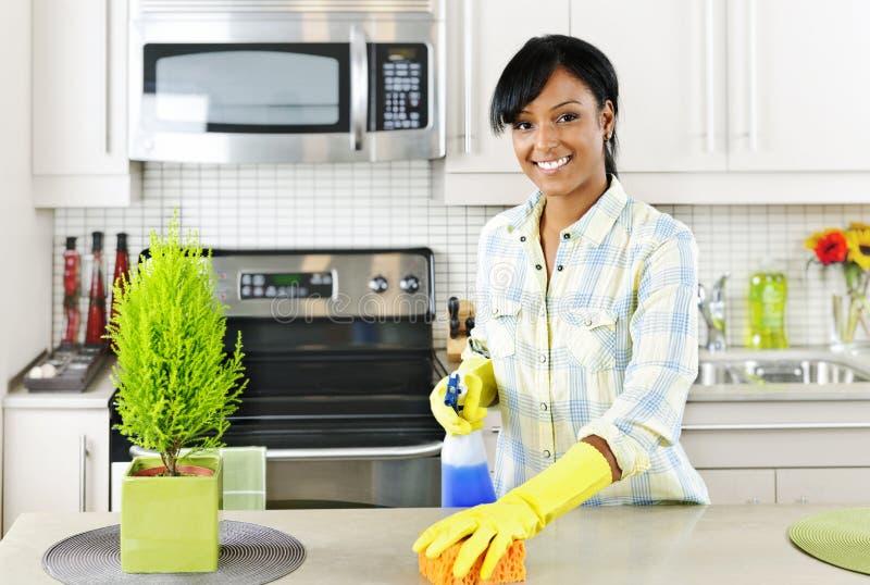 Cozinha da limpeza da mulher nova foto de stock royalty free