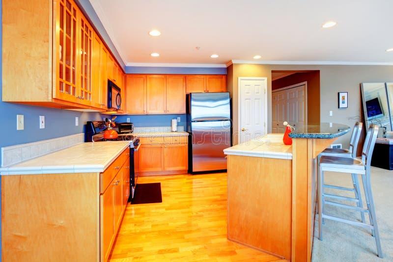 Cozinha de madeira alaranjada do apartamento da cidade com tamboretes de barra. foto de stock royalty free