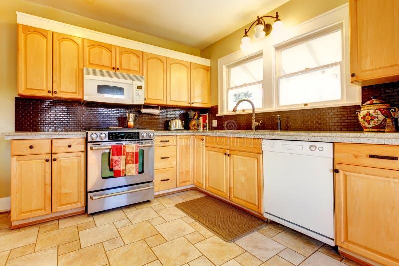 Cozinha de madeira dos tons da luz com projeto do backsplash do tijolo fotos de stock royalty free