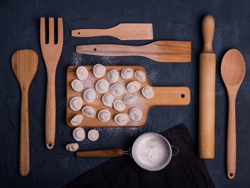 Cozinha de madeira escura da opinião superior do ravioli do russo de Dumplinga que cozinha a farinha da tabela da arte foto de stock
