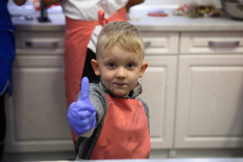A cozinha do funcionamento do avental da criança faz pirulitos dos doces imagem de stock royalty free