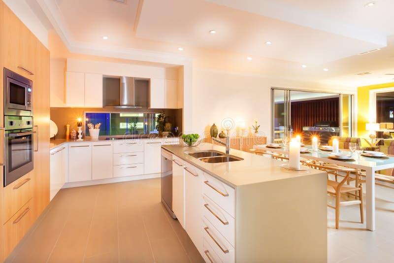 Cozinha e espaço para refeições iluminados por luzes de teto e por flashi imagens de stock royalty free
