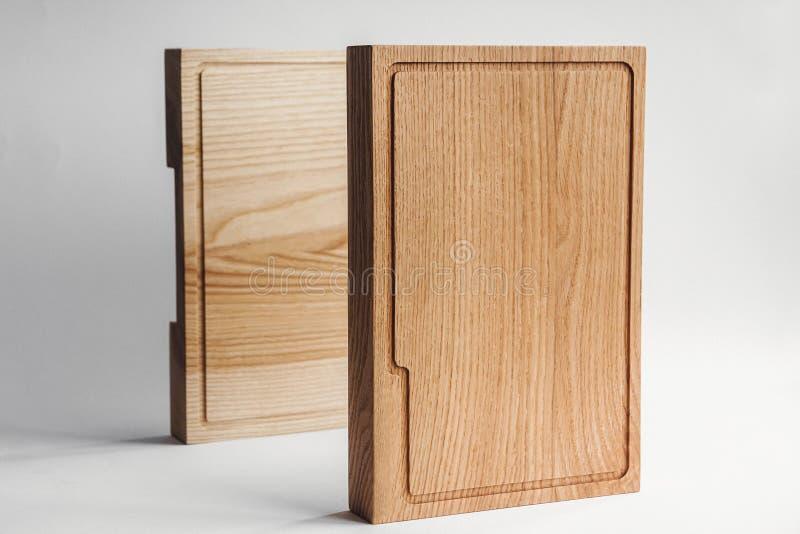 Cozinha e kitchenware Louça e utensílio rústicos e ásperos Duas placas de corte de madeira ásperas pela parede branca imagem de stock