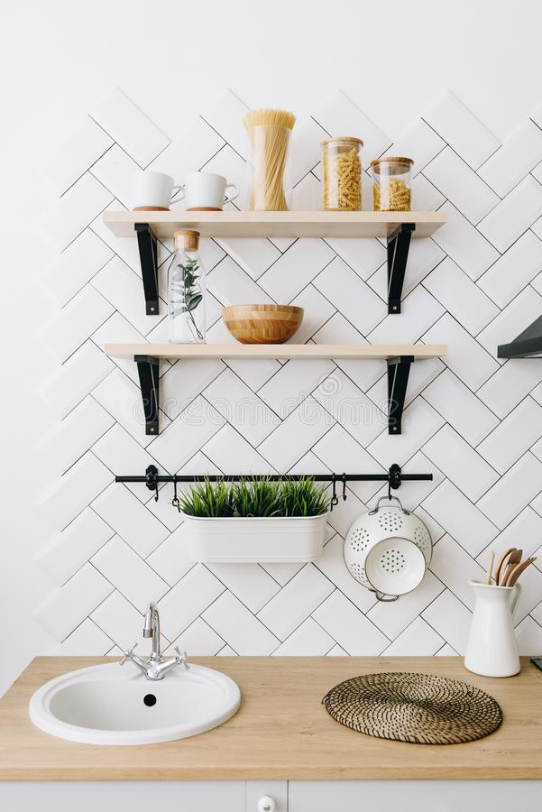 Cozinha escandinava moderna espa?oso do s?t?o com telhas brancas e os dispositivos pretos Interior moderno Prateleiras com recipi fotografia de stock