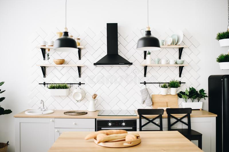 Cozinha escandinava moderna espa?oso do s?t?o com telhas brancas e os dispositivos pretos Interior moderno Baguettes em uma plant foto de stock royalty free