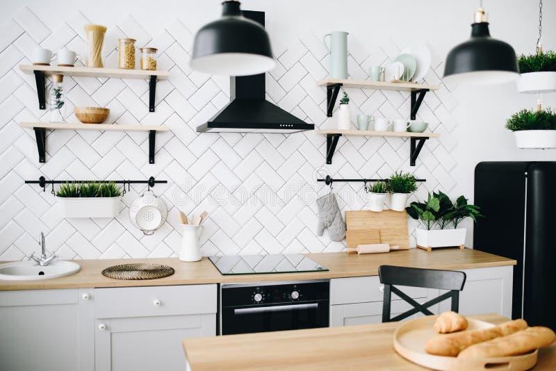 Cozinha escandinava moderna espa?oso do s?t?o com telhas brancas e os dispositivos pretos Quarto brilhante Interior moderno imagem de stock royalty free