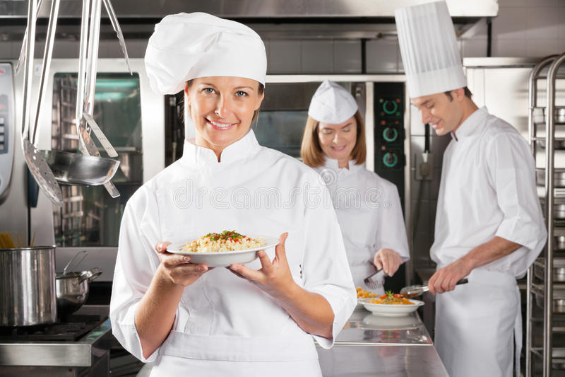 Cozinha industrial de Presenting Dish In do cozinheiro chefe feliz imagem de stock royalty free