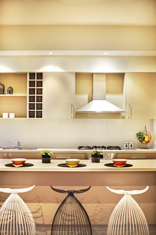 Cozinha moderna com cadeiras criativas e parte superior contrária fotografia de stock