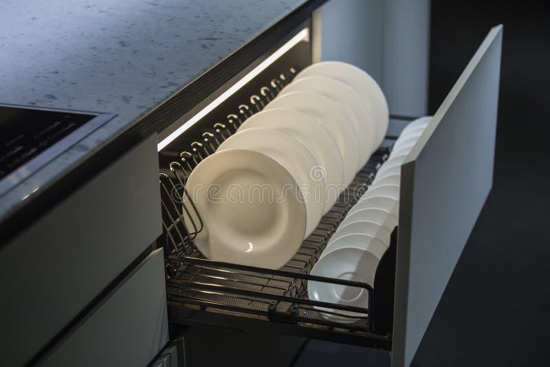Cozinha moderna, espaço de armazenamento para placas, gaveta iluminada na cozinha luxuosa foto de stock royalty free