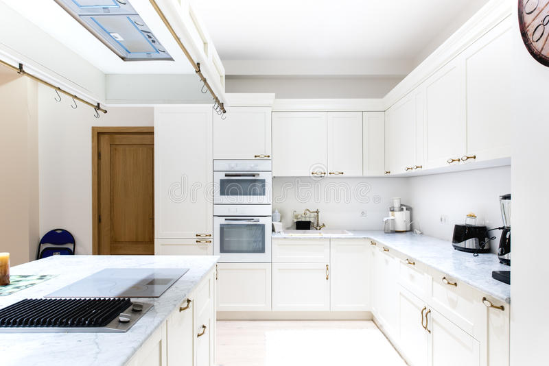 Cozinha moderna luxuoso Armários brancos da mobília de madeira na decoração home Ilha dos dispositivos, do dissipador e de cozinh imagens de stock