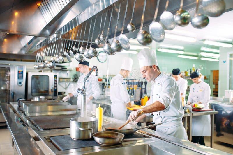 Cozinha moderna Os cozinheiros chefe preparam refeições na cozinha do restaurante fotos de stock royalty free