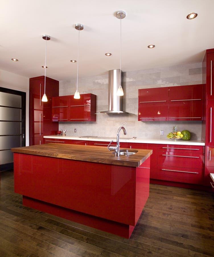Cozinha moderna vermelha contemporânea com ilha e parte superior contrária de madeira fotografia de stock