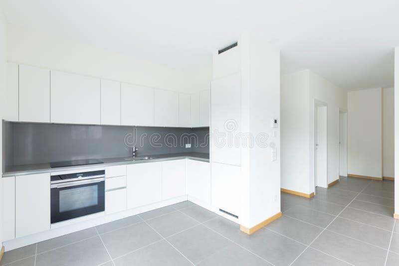 Cozinha nova, limpa e vazia na sala vazia fotografia de stock