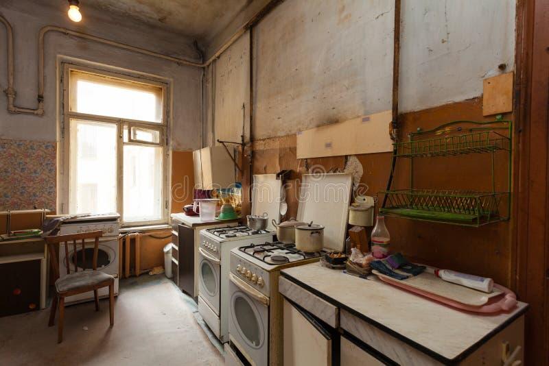 A cozinha suja com os fogões da mobília e de gás está no apartamento para os refugiados vivos provisórios da existência que foram fotos de stock