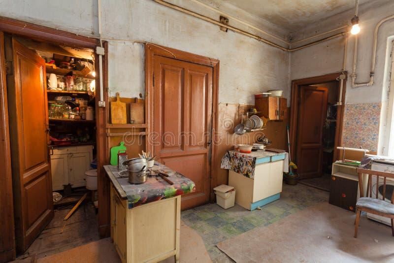 A cozinha suja com os fogões da mobília e de gás está no apartamento para os refugiados vivos provisórios da existência que foram imagens de stock