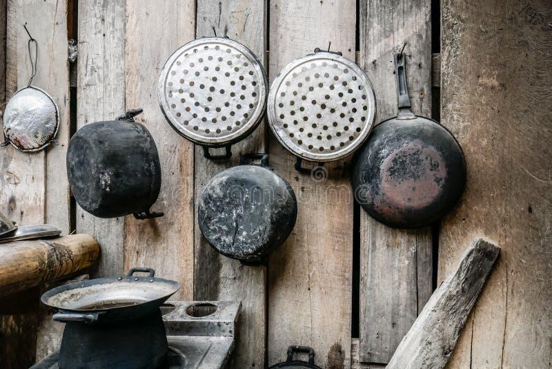 A cozinha tailandesa velha e básica com utensílios de cozimento pendurou na parede de madeira da placa fotos de stock