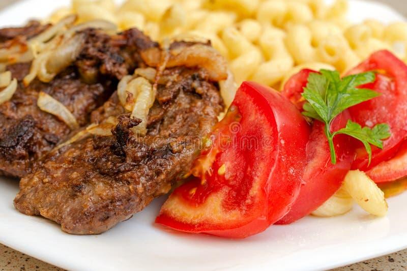 Cozinhado na massa caseiro com carne fritada da carne de porco ou da carne, e no branco imagem de stock royalty free