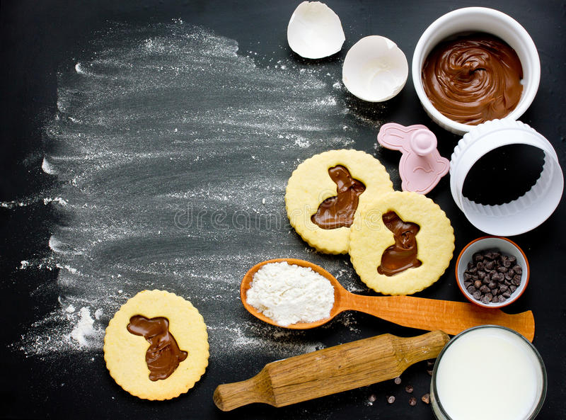 Cozinhando biscoitos da Páscoa com os ingredientes no fundo preto imagens de stock royalty free