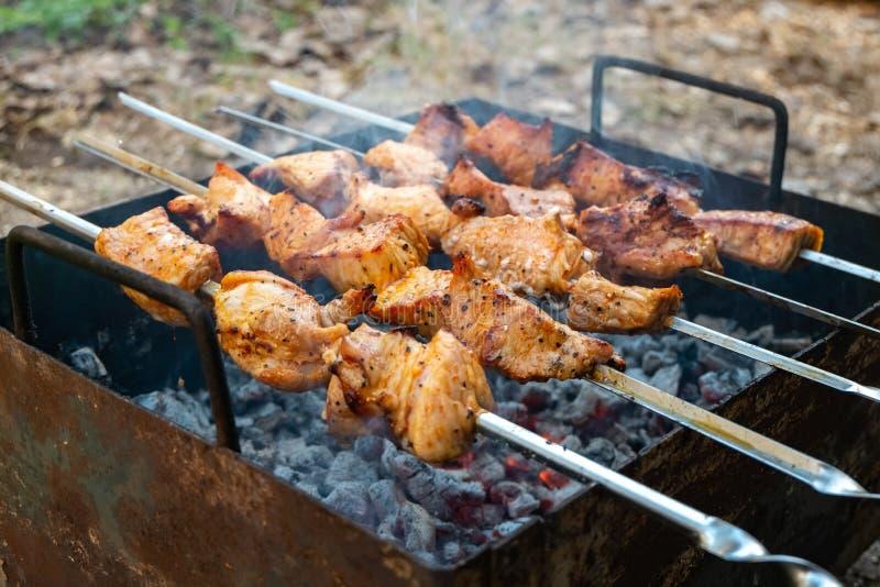 Cozinhando a carne de carne de porco no fogo Espetos com piquenique exterior da grade do BBQ do assado do shashlik fotografia de stock